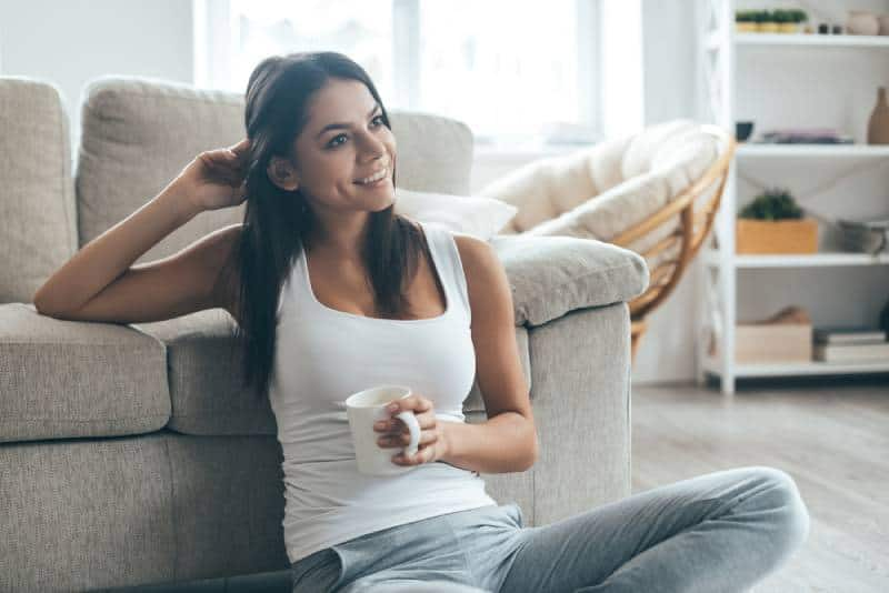 Mädchen zu Hause genießen, während auf dem Boden sitzen
