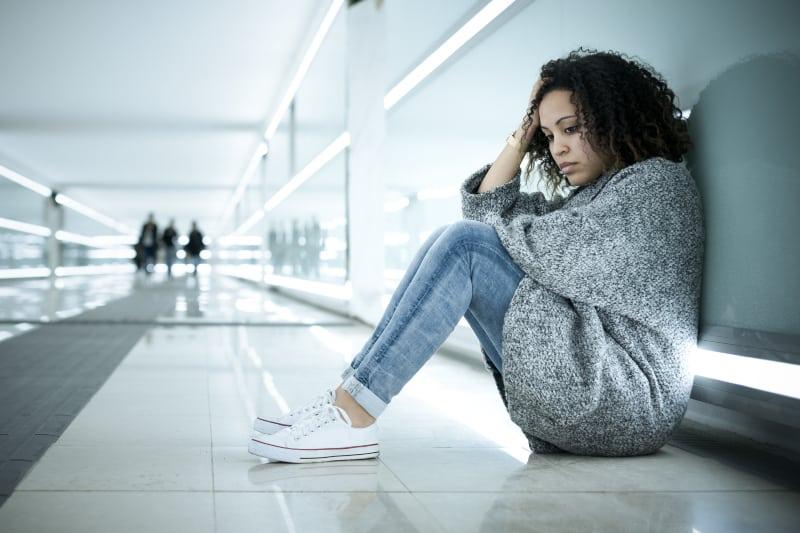 traurige Frau an eine Wand gelehnt