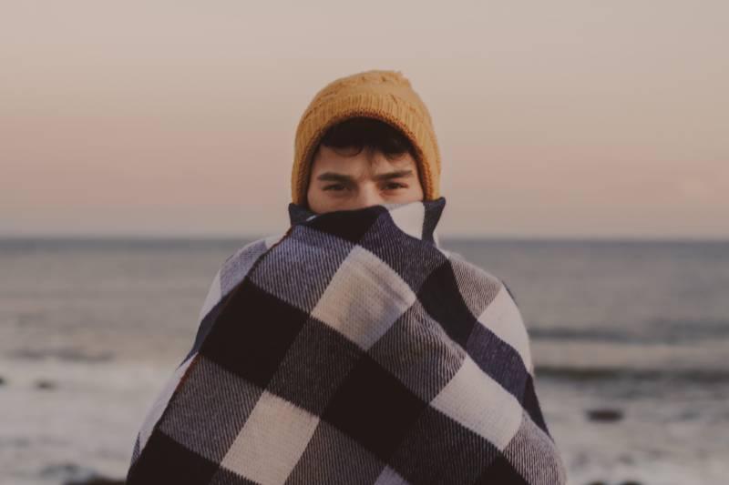 Mann bedeckt sein halbes Gesicht mit brauner Strickmütze neben dem Meer