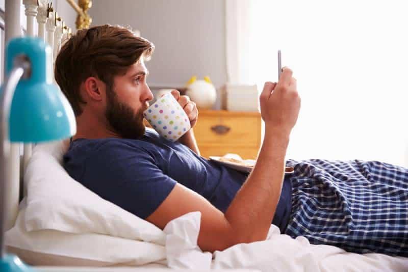 Mann, der Frühstück im Bett während der Verwendung des Mobiltelefons isst