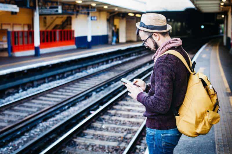 Mann, der Telefon benutzt, während er tagsüber vor Zugschiene steht