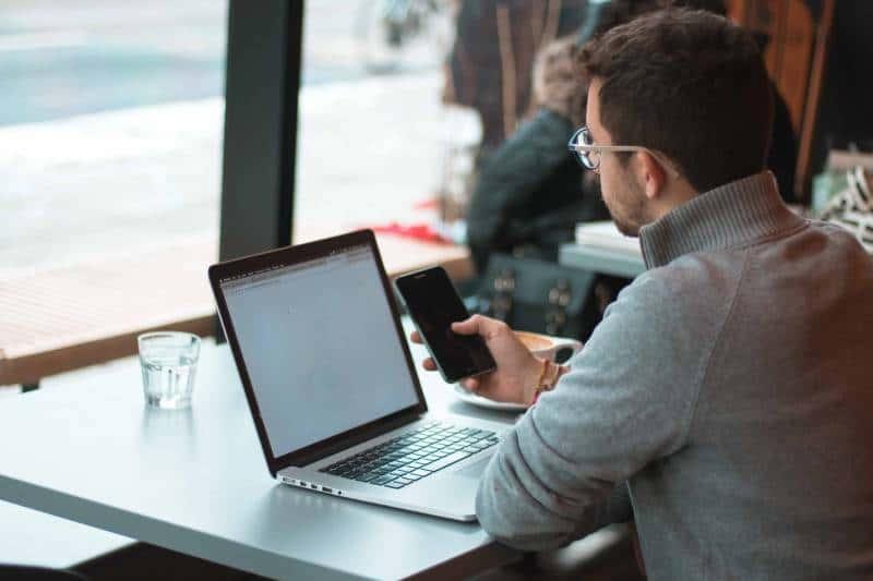 Mann, der nahe Tisch mit Laptop und Smartphone nahe Fenster sitzt