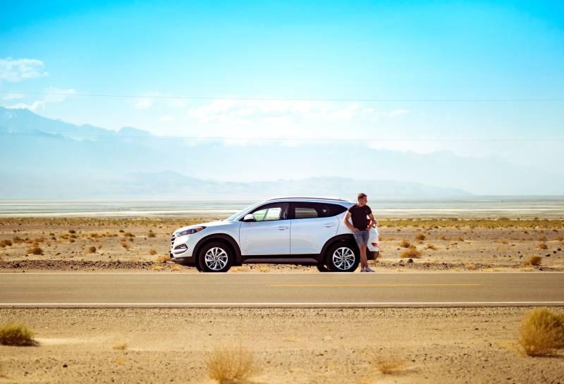 Mann, der neben weißem SUV nahe Betonstraße unter blauem Himmel am Tag steht