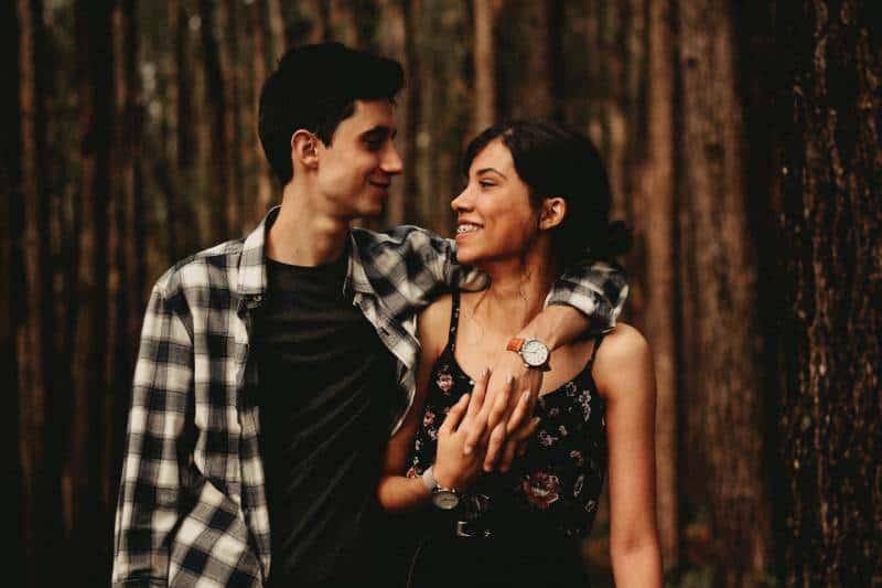 Mann, der tagsüber draußen seine Hand auf Freundin wickelt