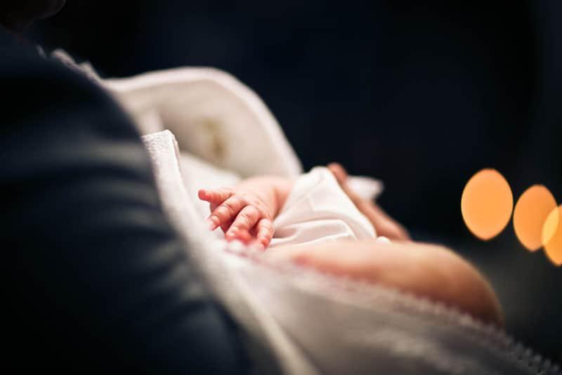 Mann hält Baby für die Taufe