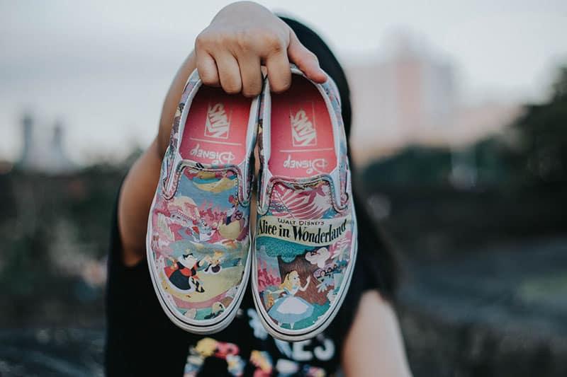 Mann hält Schuhe von Disney