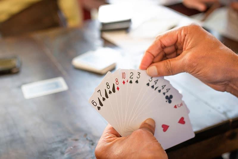 Mann hält viele Karten für das Spiel