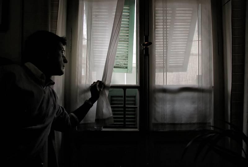 Mann hält weißen Fenstervorhang
