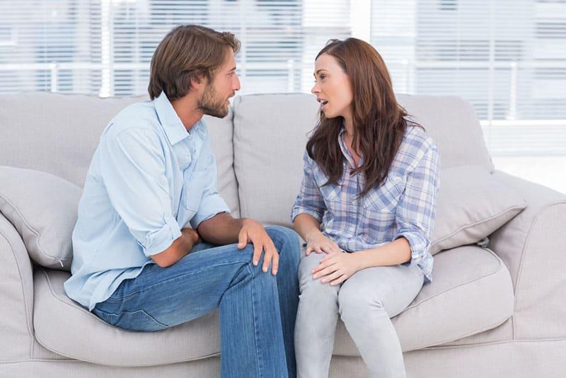 Mann hört Frau im Wohnzimmer zu