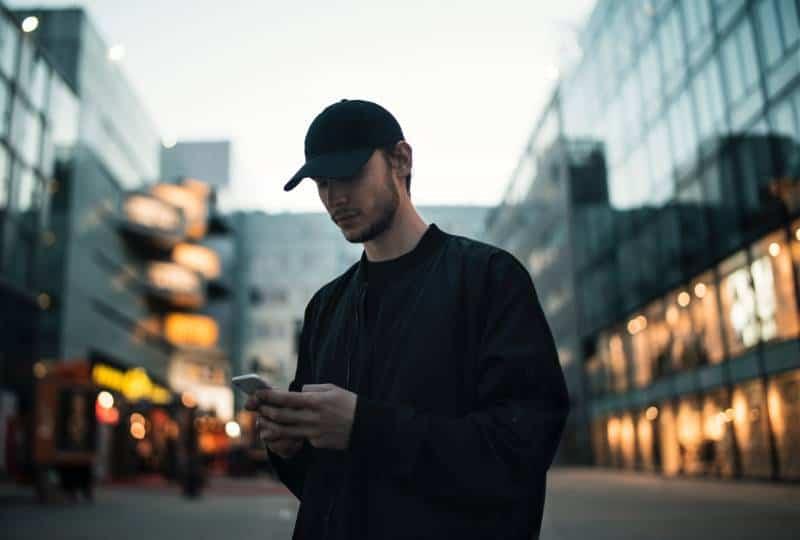 Mann in schwarzer Jacke mit schwarzer Mütze beim Telefonieren