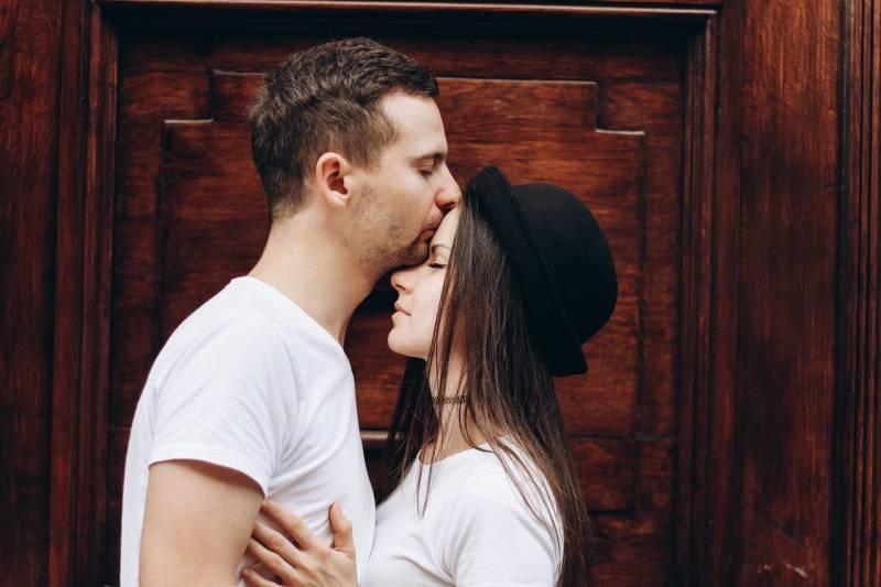 Mann küsst Frau Stirn vor Haustür