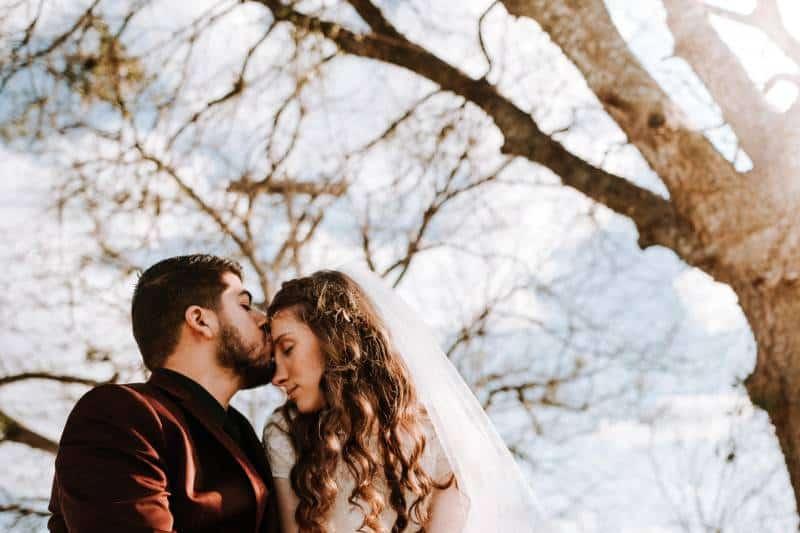 Mann küsst Frau auf ihrer Stirn nahe kahlem Baum