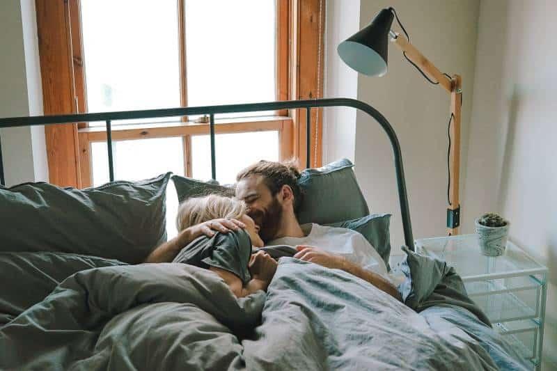 Mann küsst Frau auf ihrer Stirn, während auf Bett liegend