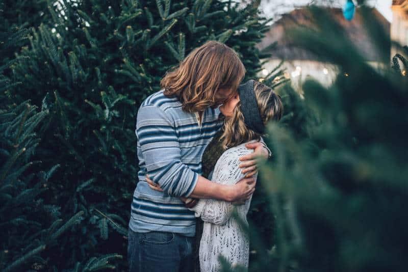 Mann küsst Frau nahe Kiefer