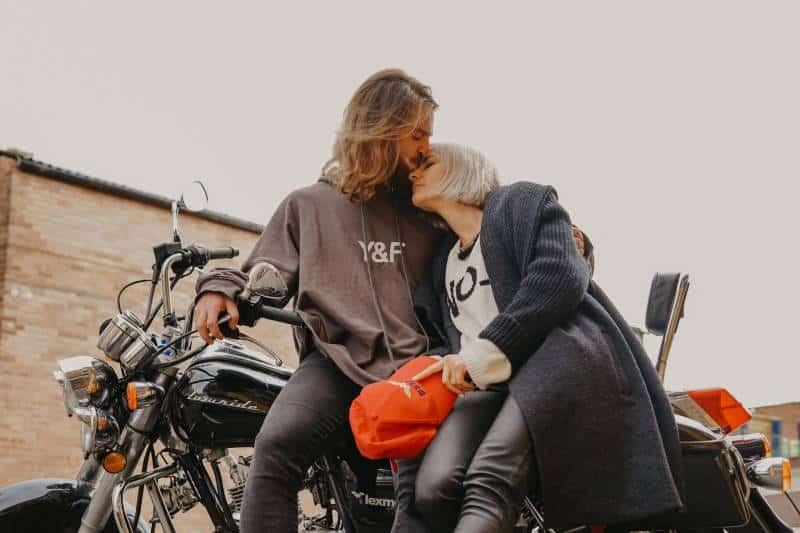 Mann küsst die Stirn der Frau beim Sitzen auf dem Motorrad
