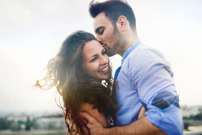 Mann küsst eine glückliche Frau