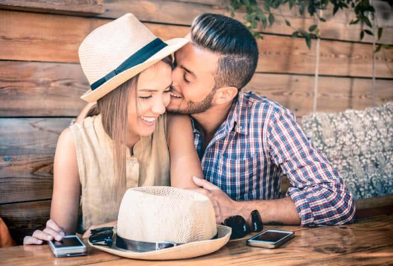 Mann küsst lächelnde Frau an der Wange am Kaffee