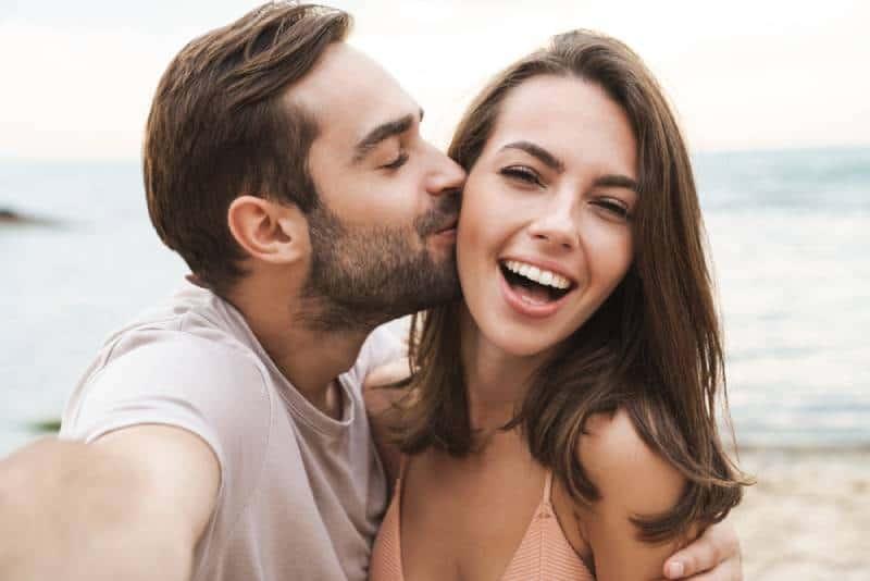 Mann küsst lächelnde Frau auf Wange beim Fotografieren
