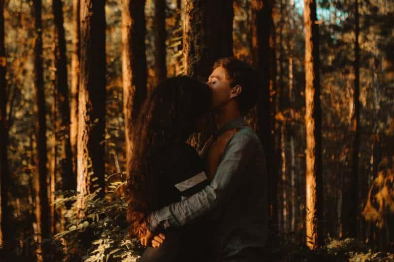 Mann küsst seine Freundin in der Stirn draußen