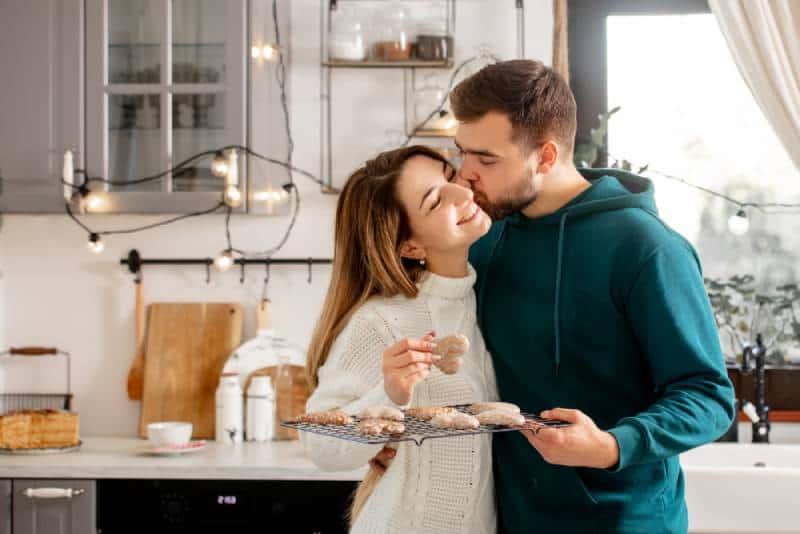 Mann küsste seine Frau auf die Wange und hielt Kekse