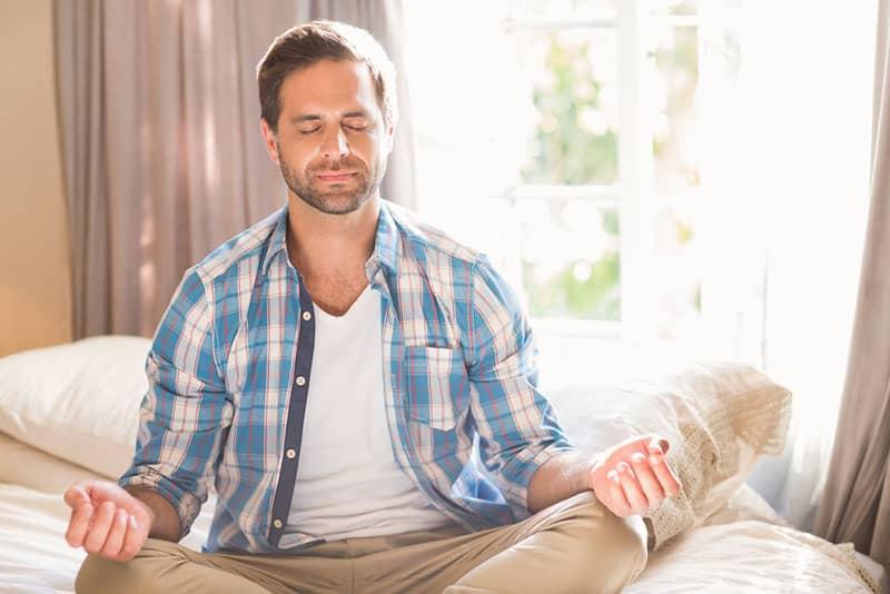Mann meditiert auf dem Bett