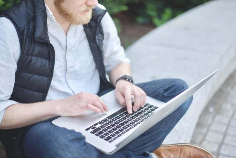 Mann mit MacBook beim Sitzen auf der Bank
