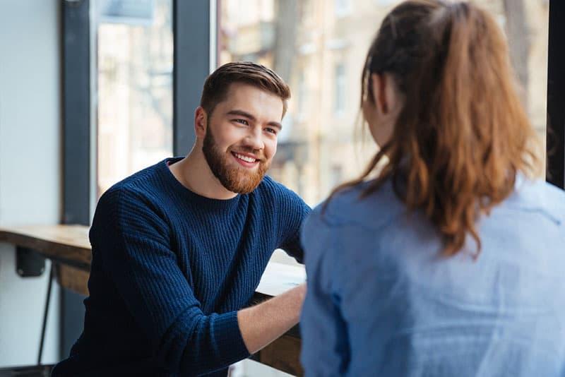 Mann mit rotem Bart hört Frau zu