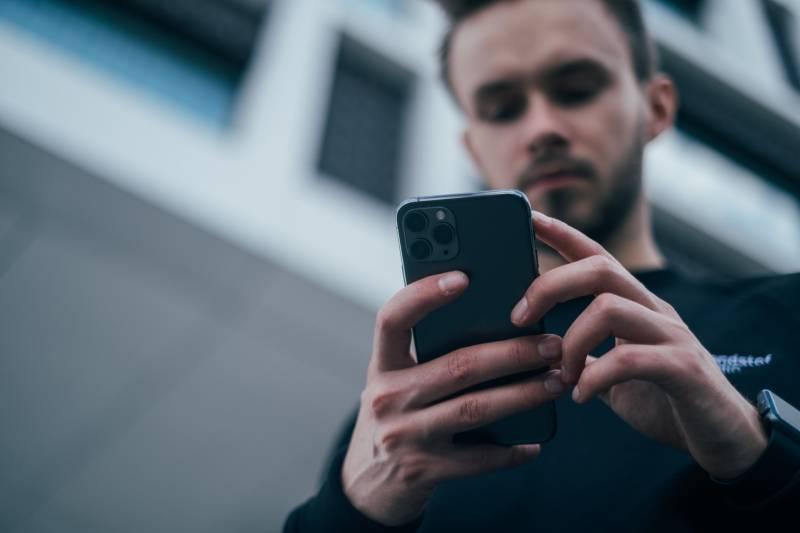 Mann schaut auf Telefon draußen
