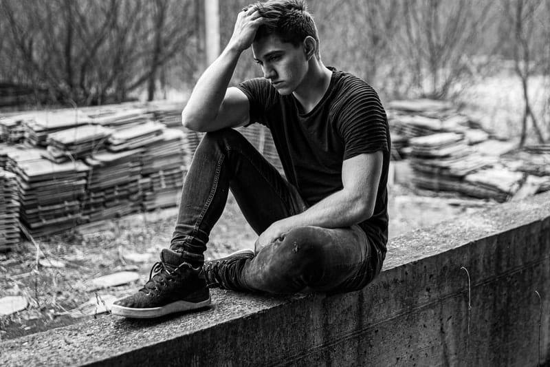 Mann sitzt auf Betonbank