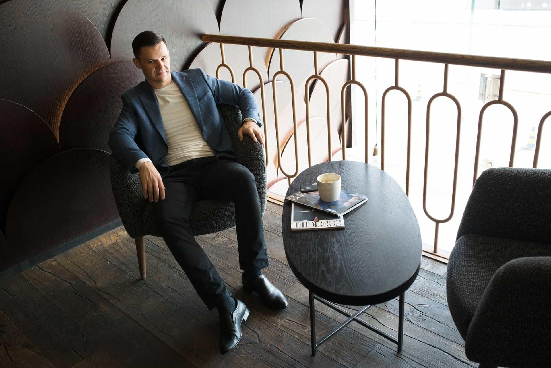 Mann sitzt auf Sofastuhl neben braunen Metallgeländern