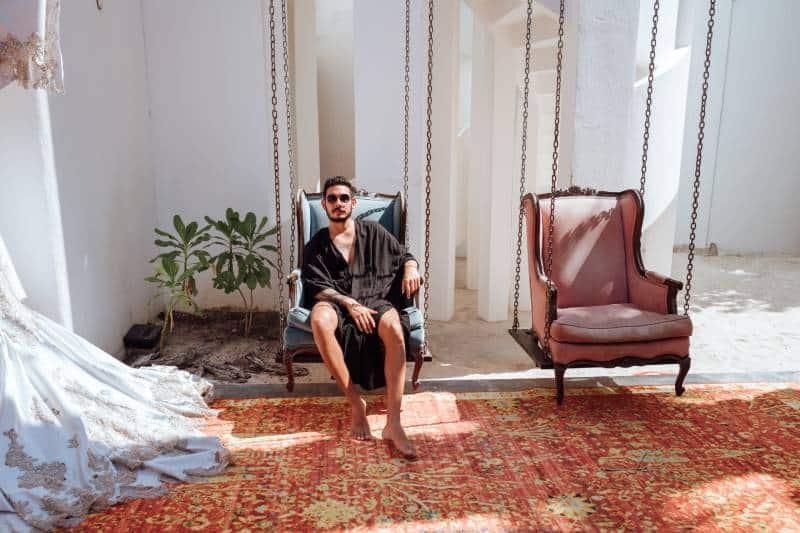 Mann sitzt auf blauem Sessel
