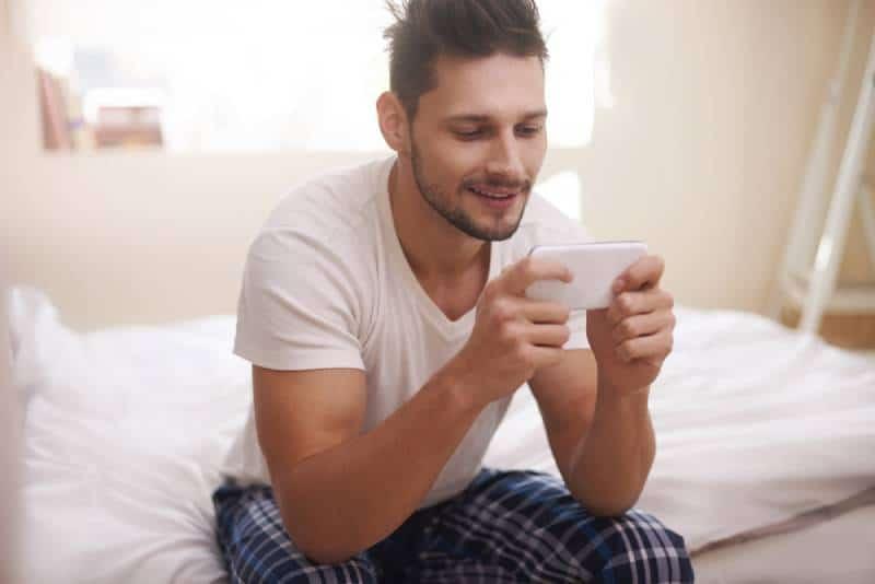 Mann sitzt und tippt morgens auf seinem Handy