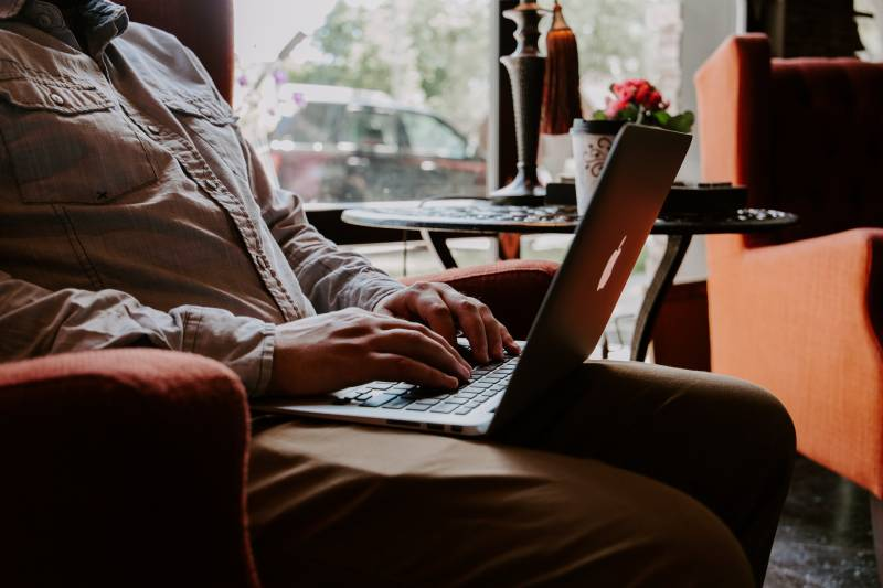 Mann sitzt, während er MacBook auf dem Schoß benutzt