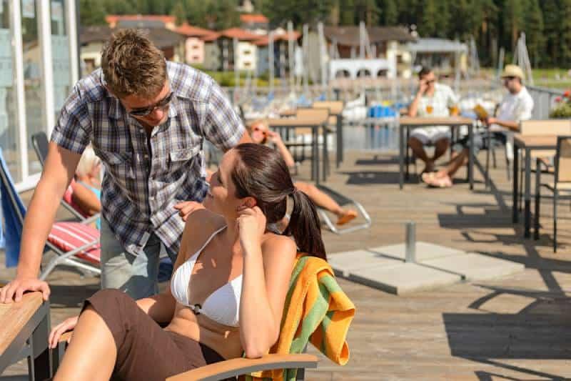 Mann spricht mit Frau draußen an der Seebar