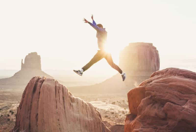 Mann springt zwischen zwei Felsen