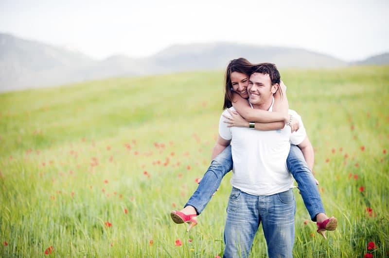 Mann trägt seine Frau auf dem Rücken