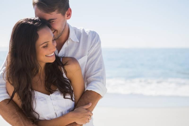 Mann umarmt seine Freundin am Strand