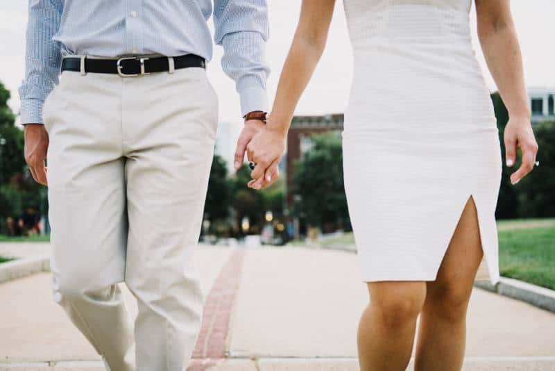 Mann und Frau Händchen haltend draußen