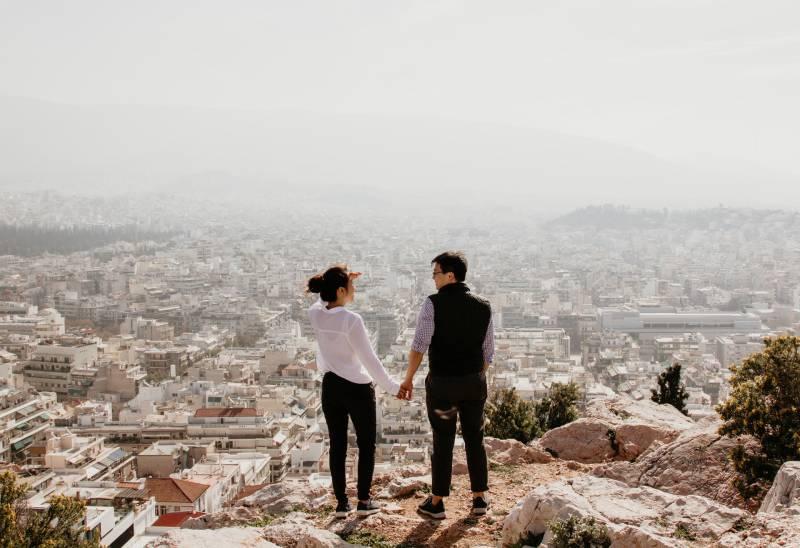 Mann und Frau auf dem Hügel halten ihre Hände