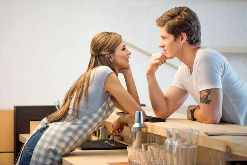 Mann und Frau flirten während der Arbeit im Café