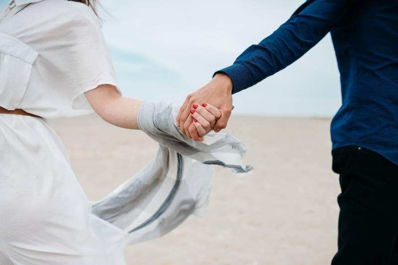 Mann und Frau halten tagsüber ihre Hände auf dem Feld zusammen