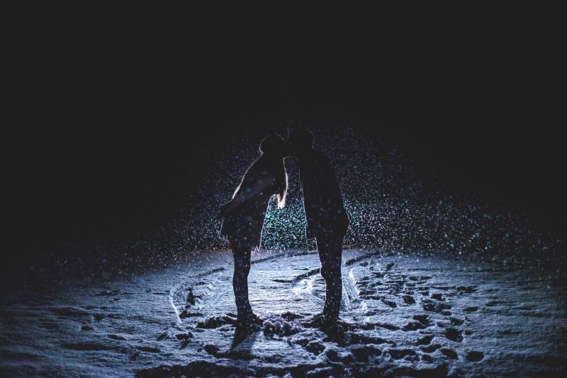 Mann und Frau küssen sich mitten im Regen