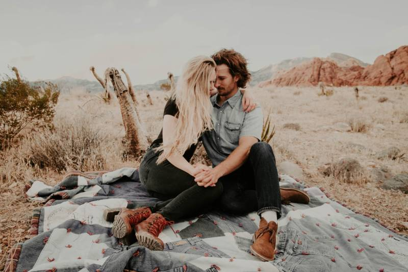 Mann und Frau sitzen auf einer Decke, während sie sich an den Händen halten