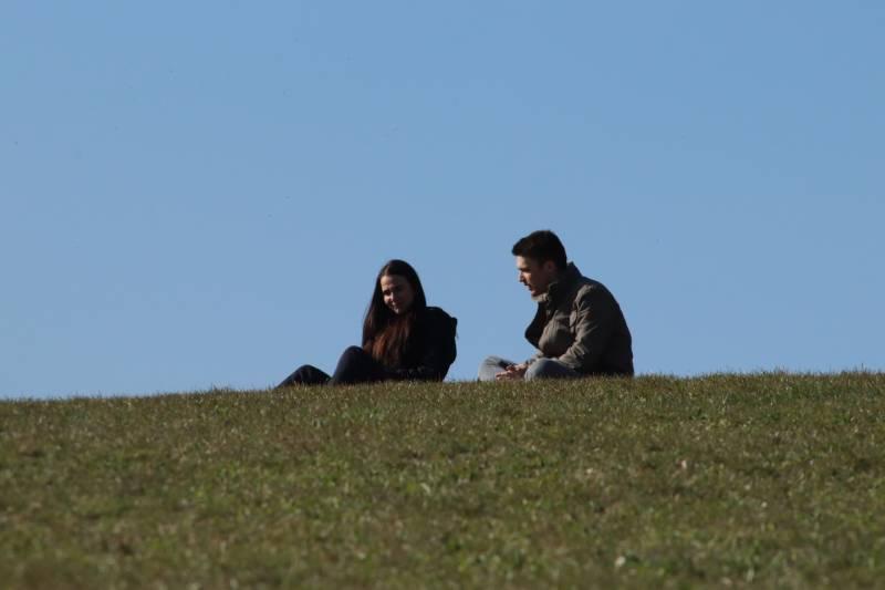 Mann und Frau sitzen auf grüner Wiese während des Tages