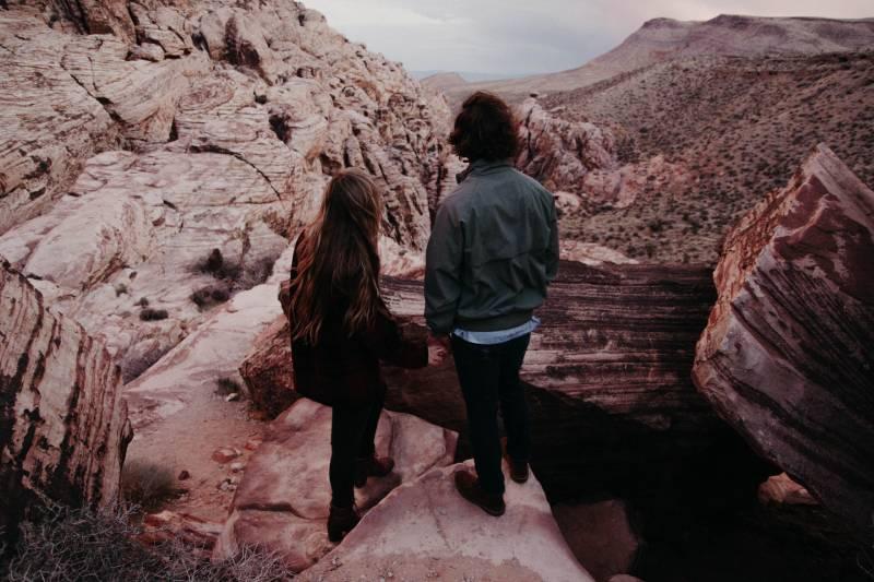 Mann und Frau stehen auf einer Klippe vor Hügeln