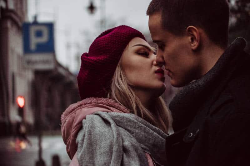 Mann und Frau stehen beim Küssen neben der Straßenbeschilderung