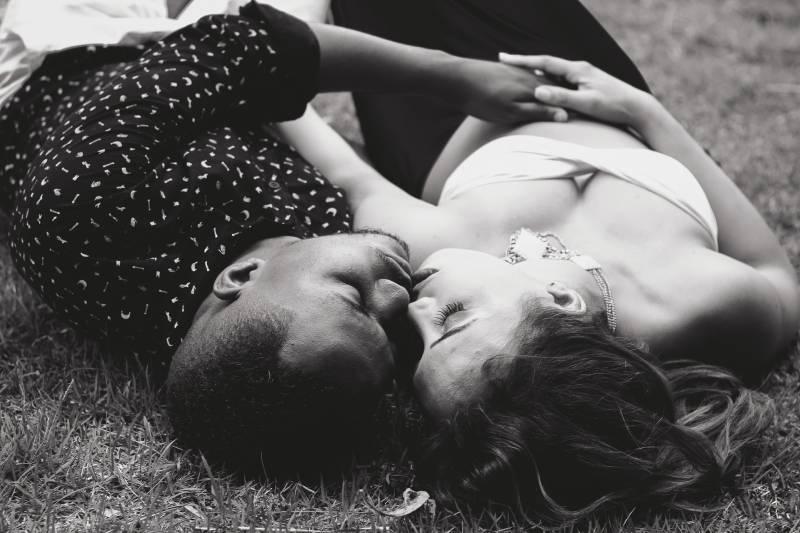 Mann und Frau stehen sich gegenüber, während sie auf Gras liegen