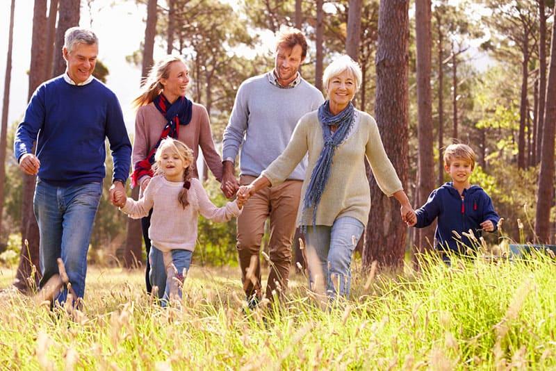 Mehrgenerationenfamilie, die durch Holz geht