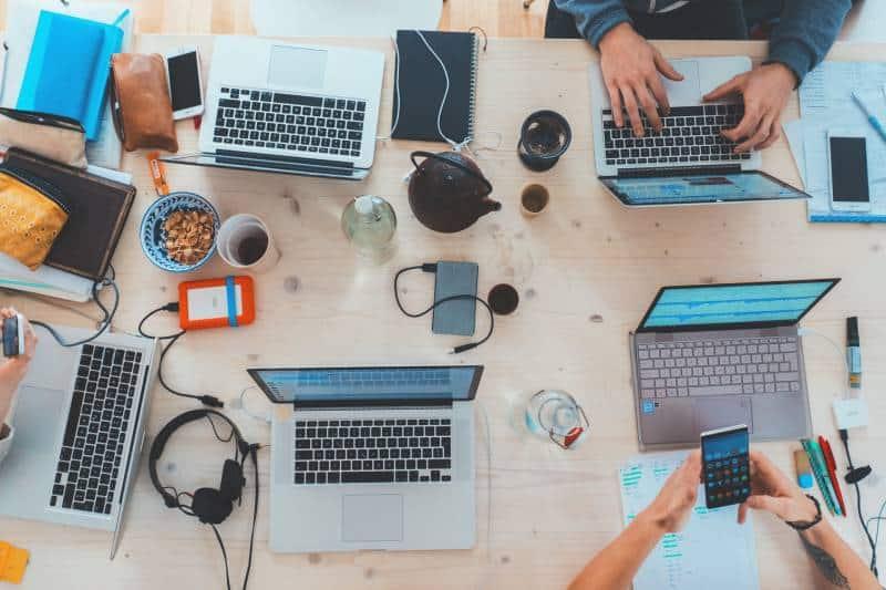 Menschen, die mit verschiedenen Laptop-Computern am Tisch sitzen