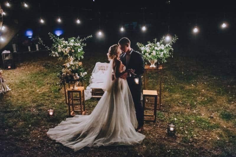 Modische Jungvermählten stehen nachts vor der Kulisse
